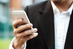 Close-up smart Business man wearing modern black suit and white shirt and texting on mobile smart phone. Close-up smart Business man wearing modern black suit Stock Images