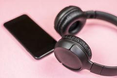 Close-up of smart phone with headphones on a pink background. stock photos