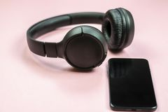 Close-up of smart phone with headphones on a pink background. royalty free stock image
