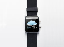 Close up of smart watch with weather forecast app. Modern technology, weather cast, object and media concept - close up of black smart watch with forecast Royalty Free Stock Images