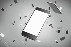 Close up of a smartphone with a blank screen. Smaller phones at the gray background. Stock Photos