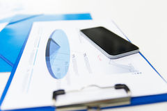 Close up of smartphone and clipboard with charts Royalty Free Stock Images