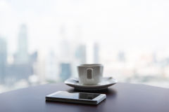 Close up of smartphone and coffee cup on table Stock Photo