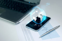 Close up of smartphone with earth globe hologram Stock Image