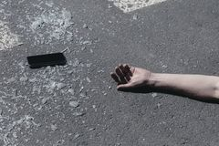 Smartphone and hand of a victim after traffic accident royalty free stock photos