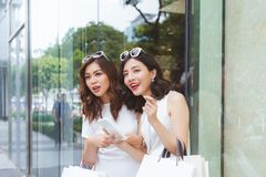 Young beautiful happy women with bags shopping with a smart phone in the street stock images