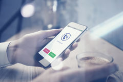Close up of smartphone holding in female hand. Cup espresso on the table, horizontal. Phone calling icons screen Stock Image