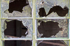 Close up of smashed panes of glass in a window Royalty Free Stock Photo