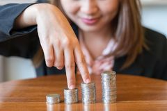 Close up smile business woman with savings coins on table - finance concept stock images