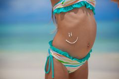 Close-up smile painted by sun cream on little. Girl's stomach. This image has attached release Royalty Free Stock Photos