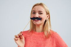 Close-up of smiley blond with fake moustache. On white Stock Image