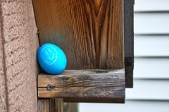 Close up of smiley face decorated egg hidden in the eaves of a shed for an Easter egg hunt in backyard. Royalty Free Stock Photo