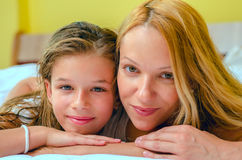 Close up of a smiley and happy girl and her mother. Close up of a young girl and her mother laying on bed Royalty Free Stock Photo
