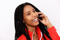 Close up smiling african girl with braided hair using cell phone on white background Royalty Free Stock Photo