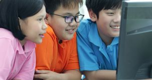 Close up of Smiling asian pupils using a desktop computer. In the classroom with smile face stock video