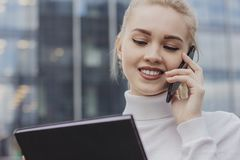 Close up of smiling attractive girl with white hair talking on mobile phone while standing outdoors near a business center royalty free stock photos