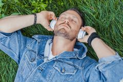 Close up of man lying on green grass and listening to music on headphones. stock image