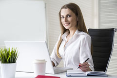 Close up of a smiling and beautiful businesswoman wearing a white blouse and sitting at her desk with a laptop. Stock Image