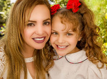 Close up of a smiling beautiful mom hugging her pretty daugher in beige dress wearing two red ties in hair.  Stock Images