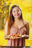 Close up of smiling beautiful young woman holding in her hands a grilled sausages on wooden cutting board, BBQ in the. Garden. Bavarian sausages Stock Images