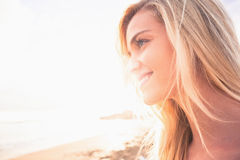 Close up of a smiling blond looking away at beach Stock Images