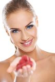 Close up of smiling blonde holding raspberries Royalty Free Stock Images