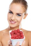 Close up of smiling blonde holding raspberries Stock Photo