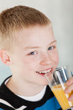 Close up on smiling boy drinking glass of juice Royalty Free Stock Photography