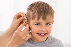 Close-up Of A Smiling Boy With Hearing Aid. Close-up Of A Doctor Fitting Hearing Aid On Smiling Boy`s Ear royalty free stock images