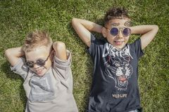 Close up of smiling boys, brothers lying on green grass. View from above. stock image
