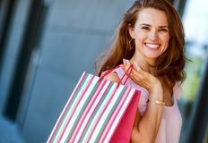 Close-up of smiling, brown-haired woman holding a stripey bag Royalty Free Stock Photos
