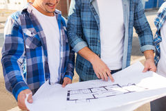 Close up of smiling builders with blueprint Royalty Free Stock Photo