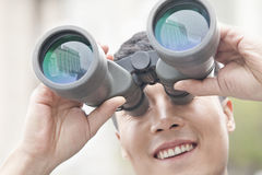 Close up of smiling businessman looking through binoculars, blue reflection in the glass Royalty Free Stock Photo