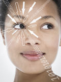 Close-up of smiling businesswoman with binary digits and arrow signs moving towards her eye against white background Royalty Free Stock Photo