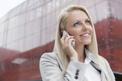 Close-up of smiling businesswoman conversing on cell phone against office building Royalty Free Stock Photos