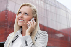 Close-up of smiling businesswoman conversing on cell phone against office building Stock Photo