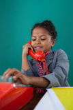 Close up of smiling businesswoman dialing numbers on land line phone. While sitting at desk against blue background Royalty Free Stock Image