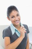 Close up of smiling businesswoman holding pen in office Royalty Free Stock Images