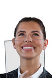 Close up of smiling businesswoman looking up while using glass interface stock photos