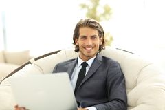 Close-up of smiling businesswoman working with laptop in living room. Royalty Free Stock Image