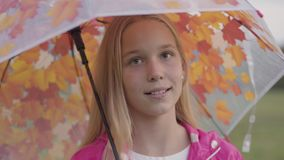 Close-up of a smiling caucasian girl with blonde hair and light brown eyes dressed in pink jacket holding collorful. Umbrella with painted yellow leaves. Pretty stock video footage