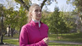 Close-up of a smiling Caucasian girl in pink sportswear and headphones running in the autumn park. Female runner. Training in the morning outdoors. Sports stock footage