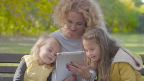 Close-up of smiling caucasian woman with blond curly hair sitting on the bench in the autumn park with two pretty little stock footage