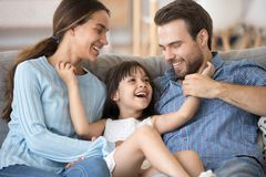 Cheerful daughter tickling parents family sitting on couch. Close up smiling cheerful daughter tickling parents people have fun playtime together at home royalty free stock photo