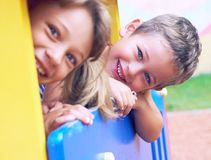 Close up of smiling childs face hiding behind wooden element of slide at playground on summer day. stock image
