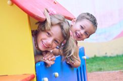 Close up of smiling childs face hiding behind wooden element of slide at playground on summer day. stock photography