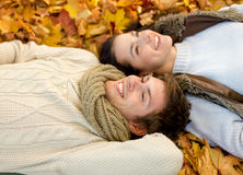 Close up of smiling couple lying in autumn park Royalty Free Stock Images