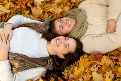 Close up of smiling couple lying in autumn park Stock Image