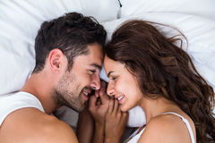Close-up of smiling couple relaxing on bed Stock Photo