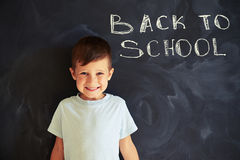 Close-up of smiling cute schoolboy near blackboard in class Royalty Free Stock Photos